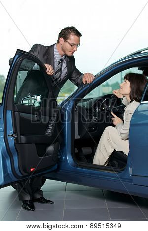 Car salesperson explaining car features to customer
