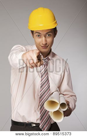 Young caucasian engineer with plans pointing finger at you
