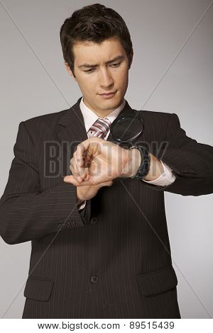 Young caucasian businessman looking on his watch with magnifying