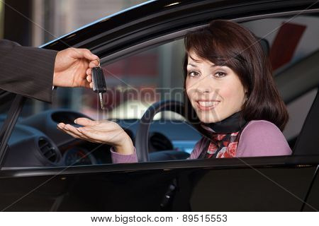 Portrait of young woman receiving the car keys from car salesman
