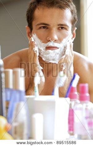 Reflection of young man in mirror applying shaving cream