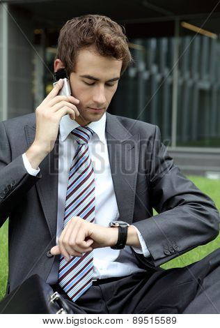 young caucasian businessman sitting on grass talking on cellphone