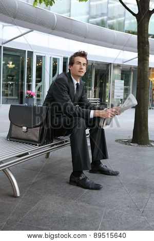 young caucasian businessman reading newspapper in office exterior