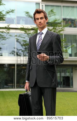 portrait of young confident caucasian businessman with cellphone