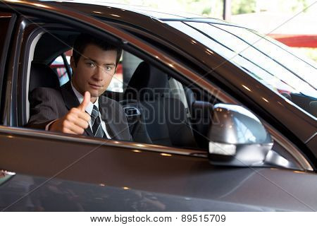 Portrait of man sitting in new car showing thumbs up