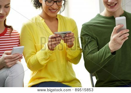 education, people and technology concept - close up of smiling students with smartphones at school