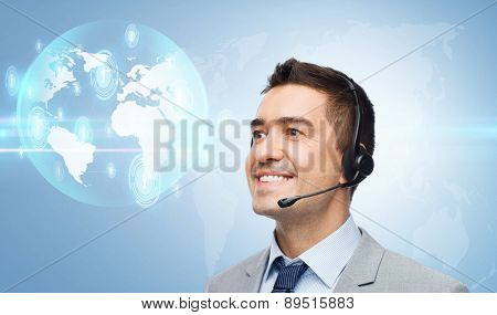 business, people, technology and service concept - smiling businessman in headset looking to virtual contacts icons projection over blue background
