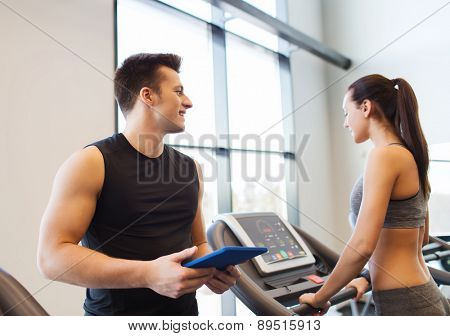 sport, fitness, lifestyle, technology and people concept - happy woman with trainer working out on treadmill in gym