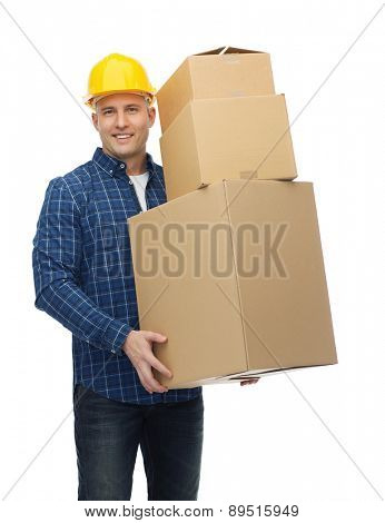 repair, building, construction, loading and delivery concept - smiling man or loader in helmet with cardboard boxes