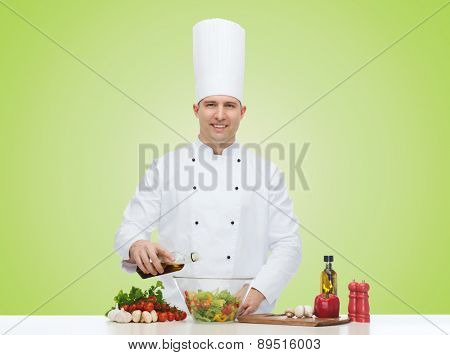 profession, vegetarian, food and people concept - happy male chef cooking vegetable salad over green background