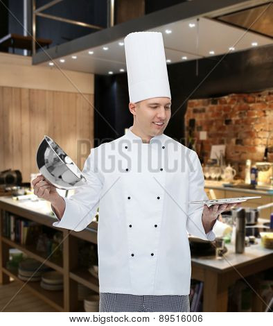 cooking, profession and people concept - happy male chef cook opening cloche cover over kitchen background