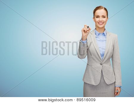 business, people and education concept - smiling young businesswoman writing something imaginary over blue background