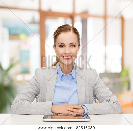 business, technology, education and people concept - smiling businesswoman sitting at table with tablet pc computer over office background