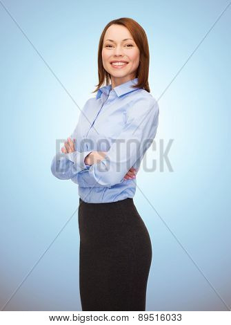 business, people and education concept - smiling young businesswoman with crossed arms over blue background