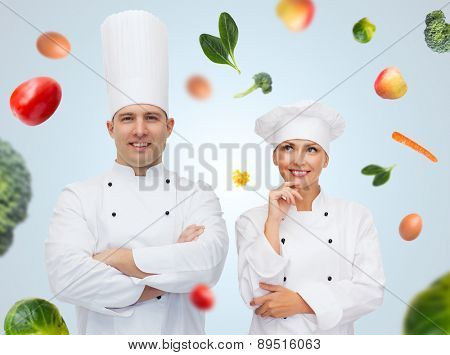 cooking, profession, vegetarian diet and people concept - happy chef couple or cooks over blue background with falling vegetables