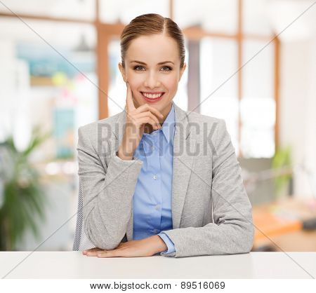 business, education and people concept - smiling businesswoman sitting at table over office background