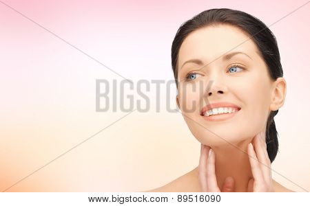 beauty, people and health concept - beautiful young woman touching her face and neck over pink background