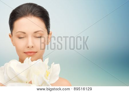 beauty, people, holidays and health concept - beautiful young woman smelling flowers with closed eyes over blue background