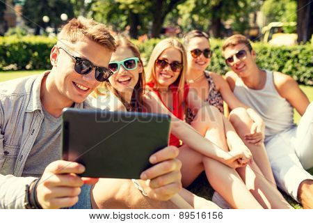 friendship, leisure, summer, technology and people concept - group of smiling friends with tablet pc computer making selfie in park