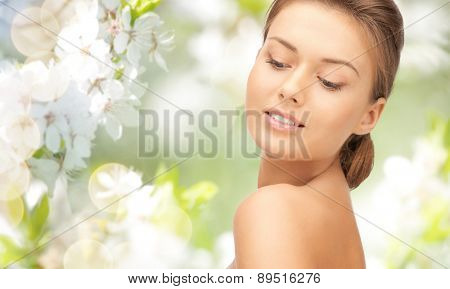beauty, people and health concept - beautiful young woman face over green blooming garden background