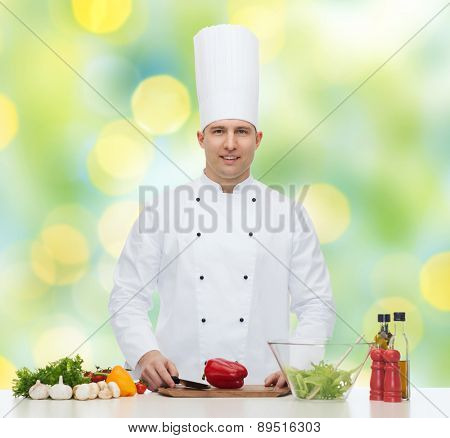 profession, vegetarian, food and people concept - happy male chef cooking vegetable salad over green lights background
