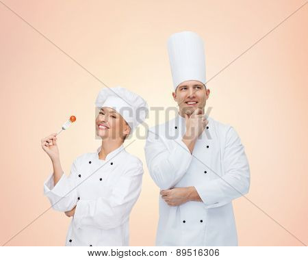cooking, profession, teamwork, inspiration and people concept - happy chefs or cooks couple over beige background