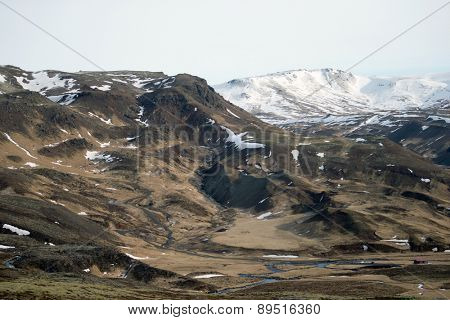 View of snow covered mountains and grass plains in southern Iceland during winter.