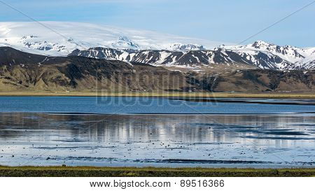 View of snow covered mountains, hills and lake in southern Iceland during winter.