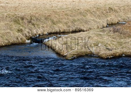 close up view of a river and grass banks with ice and snow in the water.