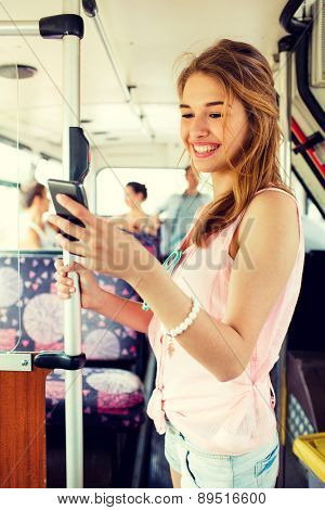 travel, vacation, summer, transport and people concept - smiling teenage girl with smartphone going by bus