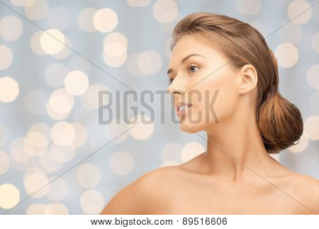 beauty, people, holidays, luxury and health concept - beautiful young woman face looking aside over lights background