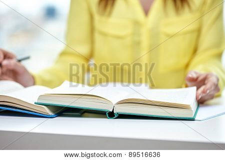 people and education concept - close up of female hands to book or textbook at school