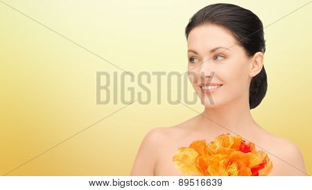 beauty, people, holidays and health concept - beautiful young woman with flowers over yellow background