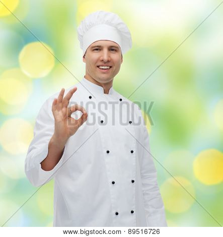 cooking, profession, gesture and people concept - happy male chef cook showing ok sign over green lights background