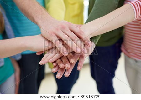 education, school, people, friendship and teamwork concept - close up of students or friends with hands on top sitting on staircase