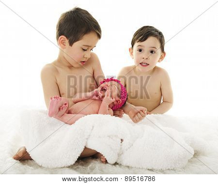 Two preschool brothers sitting with their crying newborn sister.  On a white background.