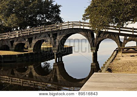 A wooden foot bridge with its reflection over a still waterway.