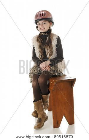 A pretty elementary horseback rider posing in her riding helmet and boots,sitting side-saddle on an old wooden bench.