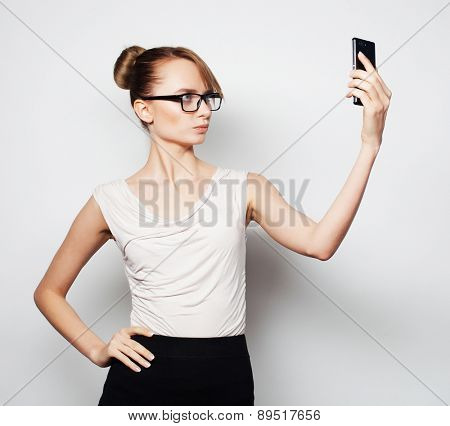 Beautiful young businesswoman holding mobile phone and making photo selfie while standing against grey background