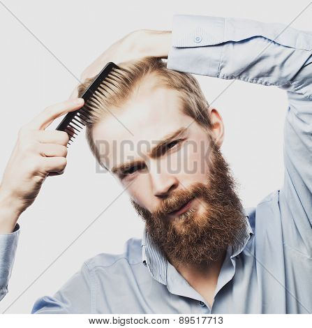 young bearded man combing his hair and looking at camera while standing against light grey background