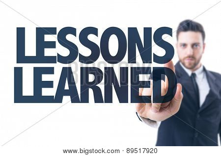 Business man pointing the text: Lessons Learned