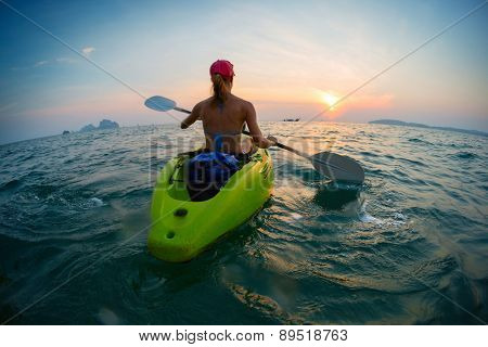 Young lady paddling the kayak in the open calm sea at sunset
