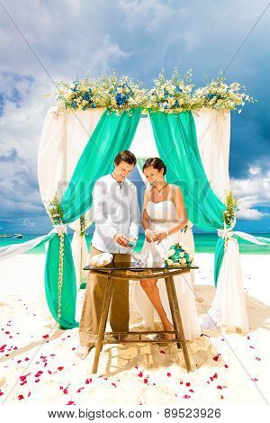 Wedding Ceremony On A Tropical Beach In Blue. Sand Ceremony. Happy Groom And Bride Under The Arch