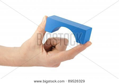 Blue Wooden Toy Bridge In Female Fingers Isolated