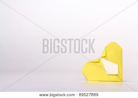 Photo of yellow origami heart with tie isolated