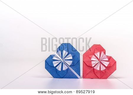 Photo of two origami hearts - blue and red.
