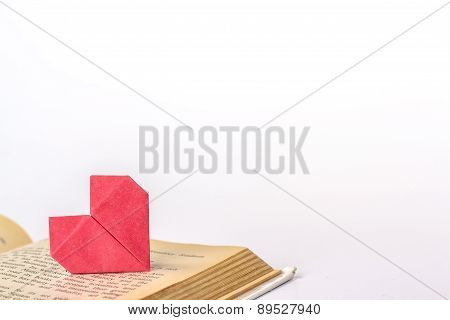 Open book with red origami heart isolated on white background