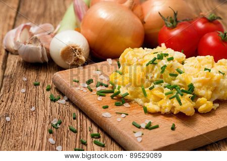 Portion Of Scrambled Eggs With Herbs On Chopping Board