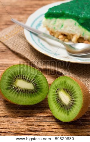 Two Halfs Of Kiwi Fruit In Front Of Green Cake