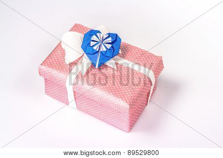 pink gift box with blue origami paper heart.